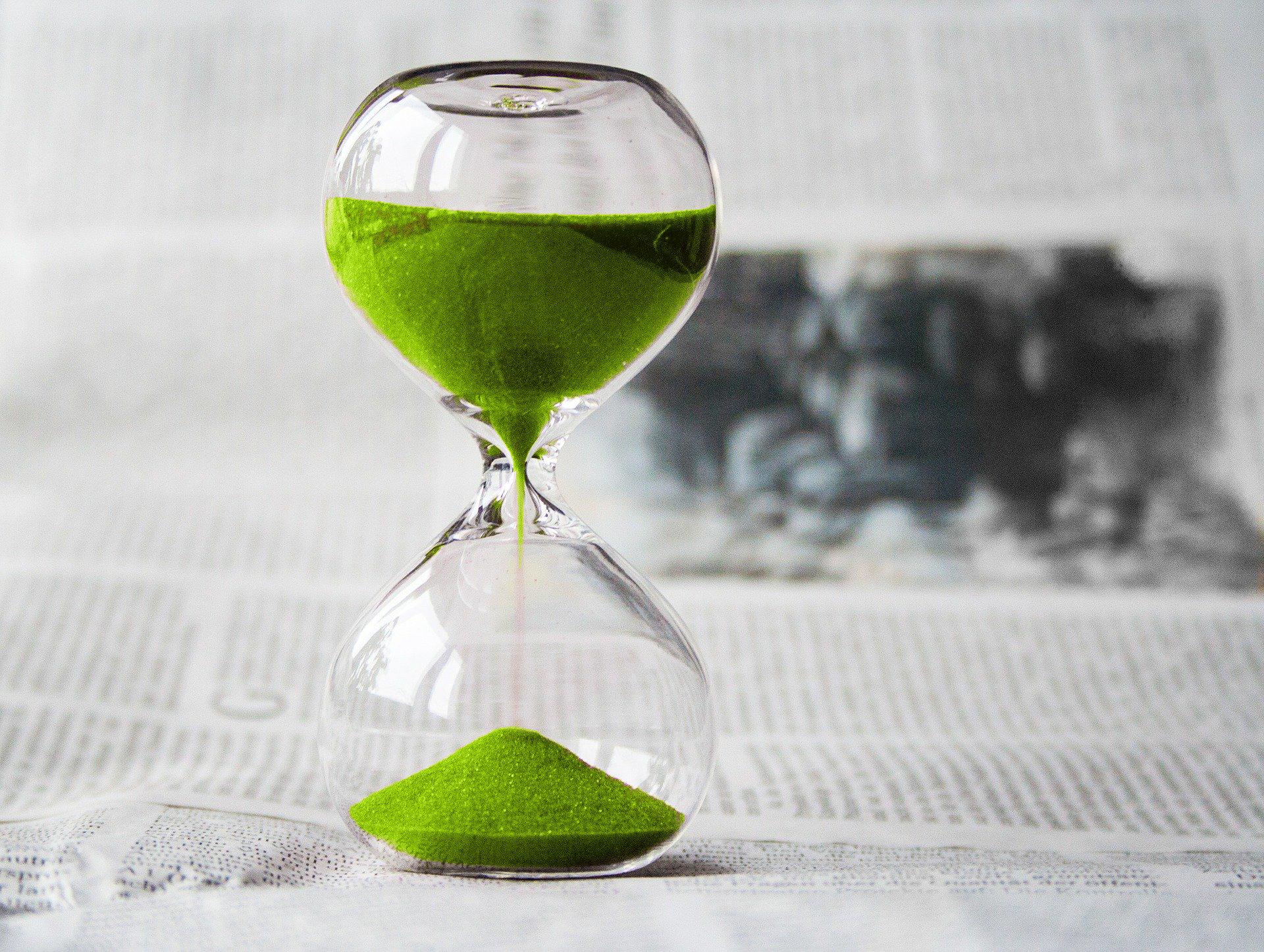 imagen de reloj de arena sobre páginas de diario